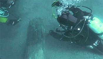 Divers attach line to submerged log